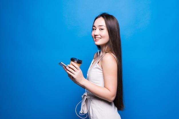 Portret azjatyckiej młodej kobiety stojącej uśmiech, używając telefonu komórkowego jej trzymając papierowy kubek z kawą, patrząc smartfona na niebieskiej ścianie