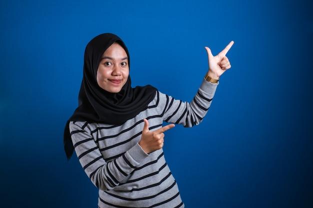 Portret azjatyckiej młodej szczęśliwej azjatyckiej muzułmańskiej studentki uśmiecha się i wskazuje na prezentację czegoś po swojej stronie, z miejscem na kopię