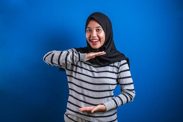 Portret azjatyckiej młodej szczęśliwej muzułmańskiej kobiety przedstawiającej coś między jej rękami, na niebieskim tle z kopią przestrzeni
