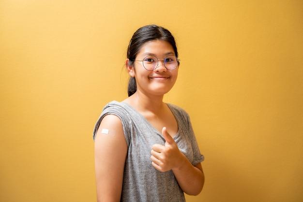 Portret azjatyckiej nastolatki dającej kciuki w górę po wstrzyknięciu szczepionki przeciw covid-19 i pokazującej bandaż na ramieniu, zaszczepione