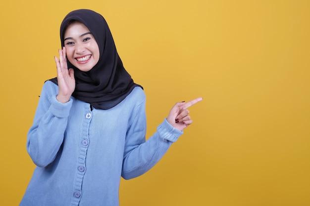 Portret azjatyckiej pięknej kobiety noszącej czarny hidżab, powiedz coś szeptem i wskazując palcem wskazującym