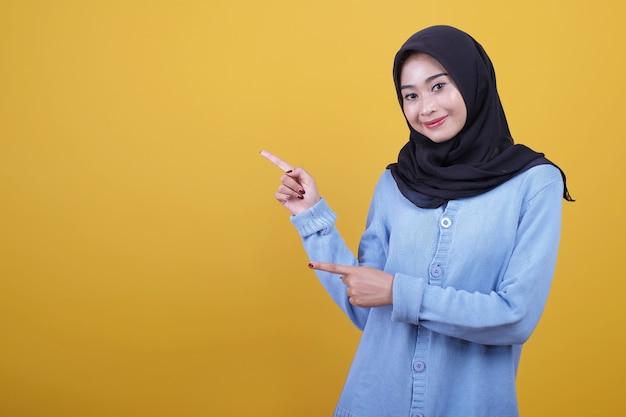 Portret azjatyckiej pięknej kobiety noszącej czarny hidżab, szczęśliwie patrzy wyrazem wskazującym palcem wskazującym
