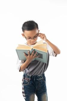 Portret azjatyckiej tajlandzkiej chłopiec studencka czytelnicza książka odizolowywająca