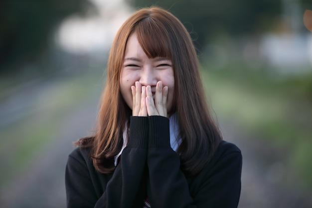 Portret azjatykci japońskiej szkoły dziewczyny kostiumowy patrzeje parkowy plenerowy ekranowy rocznika styl