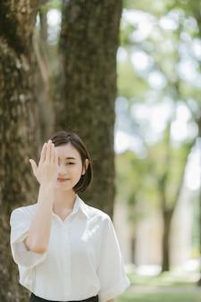 Portret azjatykci kobieta stojak zamyka oczy z jej rękami i ono uśmiecha się w parku.