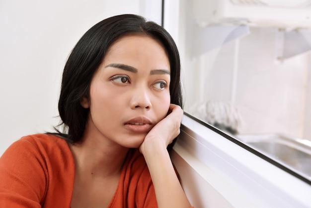 Portret azjatykci kobiety rojenie i patrzeć przez okno