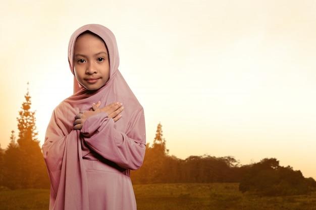 Portret azjatykci muzułmański dziecko jest ubranym przesłony pozycję