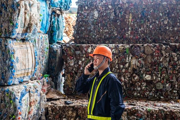 Portret azjatykci przemysłowego inżyniera pracownicy z stosem plastikowe butelki przy fabryką