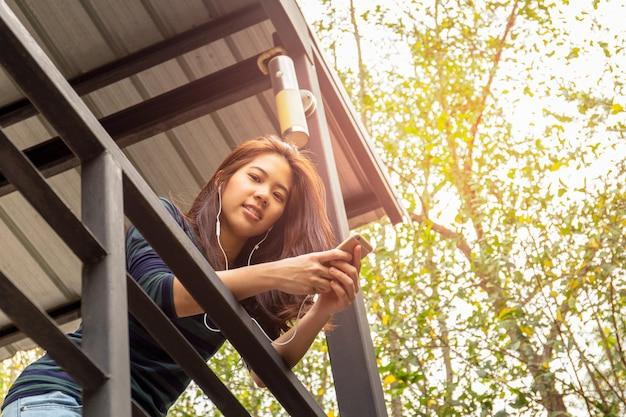 Portret azjatykcia 20s nastolatka kobieta słucha muzyka z słuchawką.