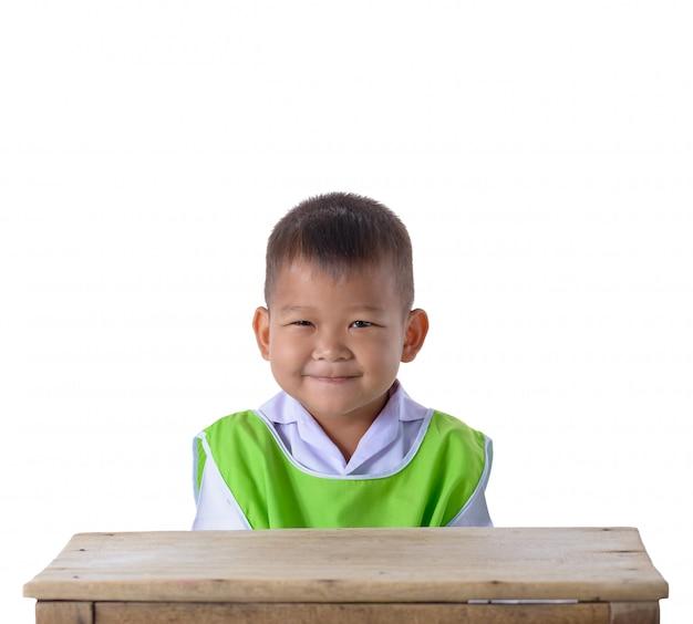 Portret azjatykcia chłopiec w mundurku szkolnym odizolowywającym na białym tle