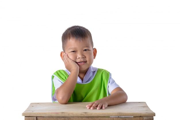 Portret azjatykcia chłopiec w mundurku szkolnym odizolowywającym na bielu