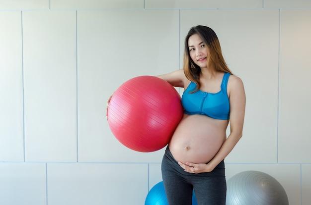 Portret azjatykcia ciężarna kobieta ćwiczy w pokoju sportowym, trzyma dużą piłkę