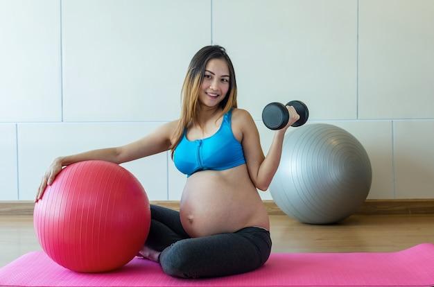 Portret azjatykcia ciężarna kobieta ćwiczy w sporta pokoju