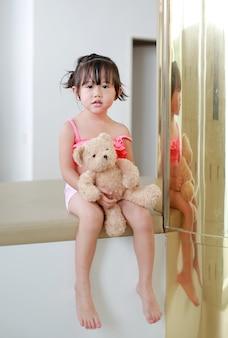 Portret azjatykcia dziecko dziewczyna w pływackiego kostiumu lying on the beach na kanapie z odbicie słupem