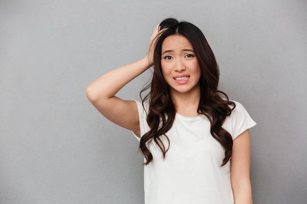 Portret azjatykcia kobieta 20s z ciemnymi kędzierzawymi włosami dotyka jej głowy i wyraża zmartwienie odizolowywającego, nad szarości ścianą