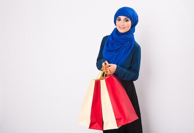 Portret azjatykcia muzułmanka z torby na zakupy na białym tle.