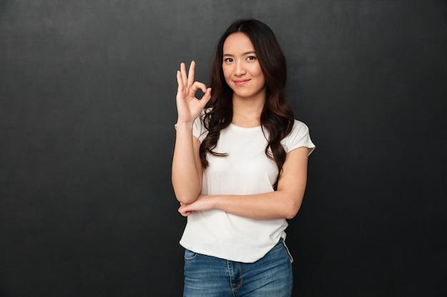 Portret azjatykcia śliczna kobieta uśmiecha się i pokazuje ok lub dobra znaka w przypadkowej koszulce i cajgach, odizolowywający nad zmrokiem - szarości ściana