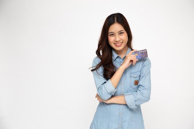 Portret azjatykcie kobiety jest ubranym błękitną cajgową koszula trzyma kredytową kartę i uśmiech odizolowywających nad biel ścianą, młoda kobieta ono uśmiecha się, szczęśliwy czuciowy pojęcie
