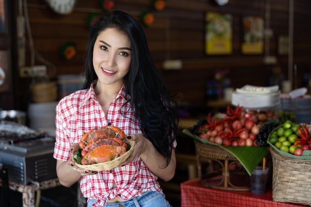 Portret azjatykcie kobiety z lejącym się krabem na ręce w amphawa rynku