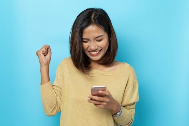 Portret azjatykcie młode kobiety są szczęśliwe podczas gdy używać smartphone odizolowywającego