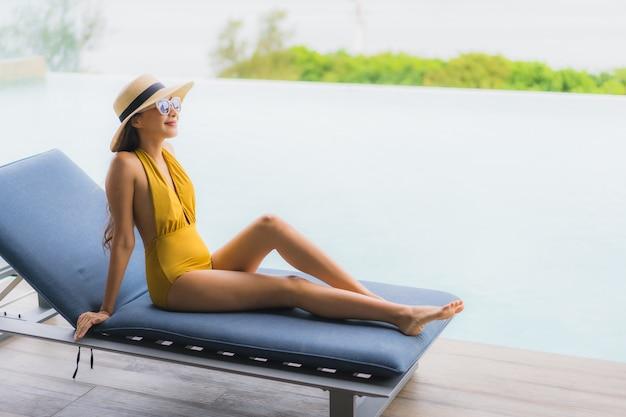 Portret azjatykciej pięknej młodej kobiety szczęśliwy uśmiech relaksuje wokoło plenerowego pływackiego basenu w wakacje wakacje