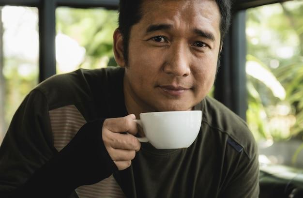 Portret azji mężczyzna w średnim wieku picia kawy w kawiarni.