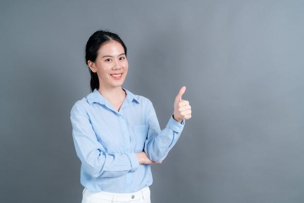 Portret azji piękna młoda kobieta stojąca, zrobiła kciuki do góry na szarej ścianie