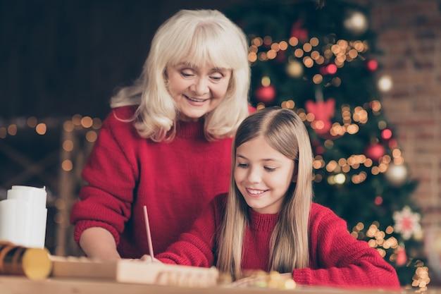 Portret babci wnuka pisania listu do czasu wigilii w urządzonych wnętrzach domu