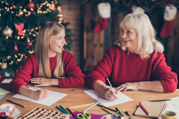 Portret babci wnuka pisze listę życzeń na stole w urządzonym domu