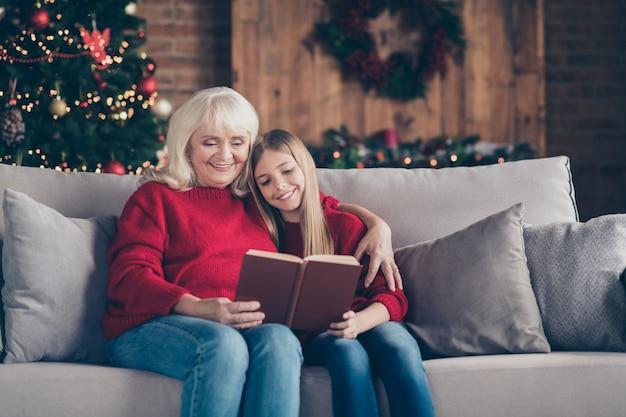 Portret babci wnuka siedzi na kanapie i czyta książkę w pomieszczeniu przemysłowym