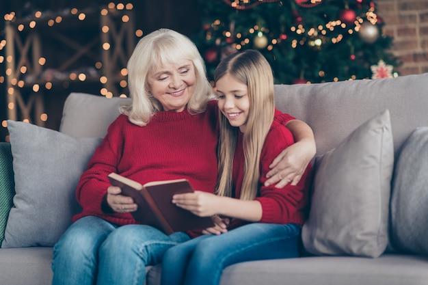 Portret babci wnuka siedzi na kanapie i poczyta bajkę w urządzonym pokoju na poddaszu