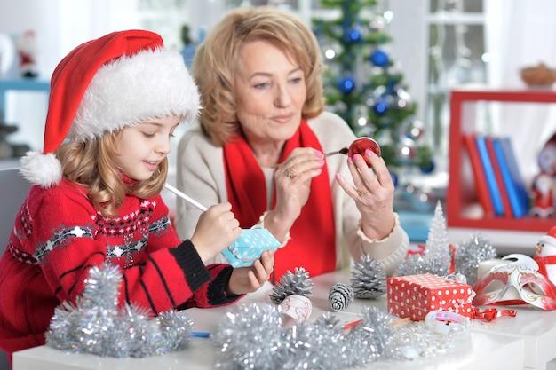 Portret babci z dziewczyną w kapeluszu świętego mikołaja przygotowuje się do świąt w domu