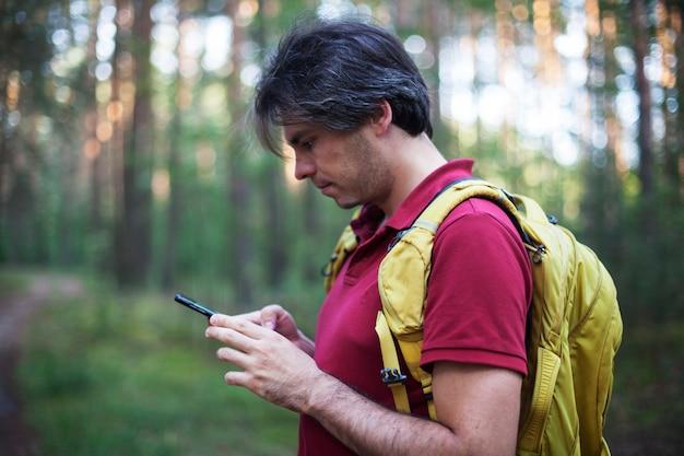 Portret backpacker patrząc na nawigator gps, urządzenie globalnego systemu pozycjonowania