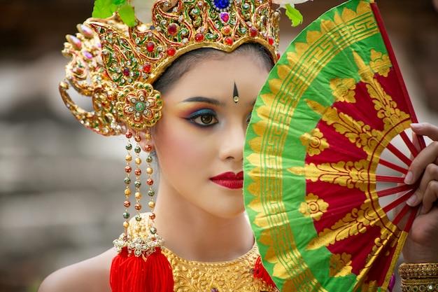 Portret balijskich tancerzy trzyma składany wachlarz
