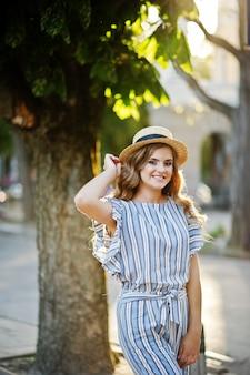 Portret bardzo atrakcyjnej młodej kobiety w pasiastym kombinezonie pozuje z kapeluszem na chodniku w mieście