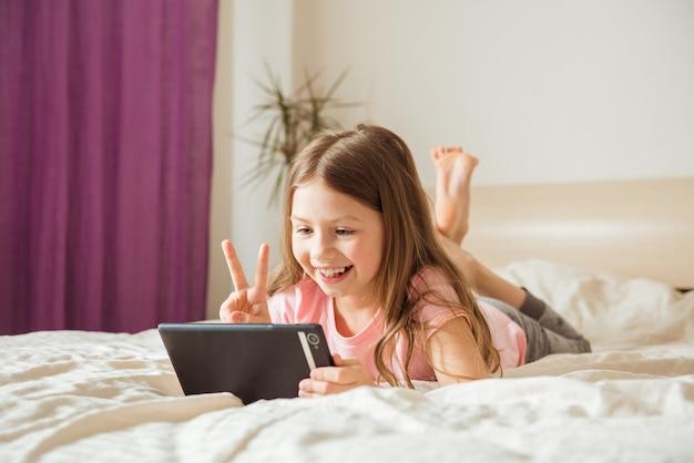 Portret bardzo pięknej dziewczynki uśmiecha się do smartfona, robi selfie lub komunikuje się z przyjaciółmi na rozmowie wideo