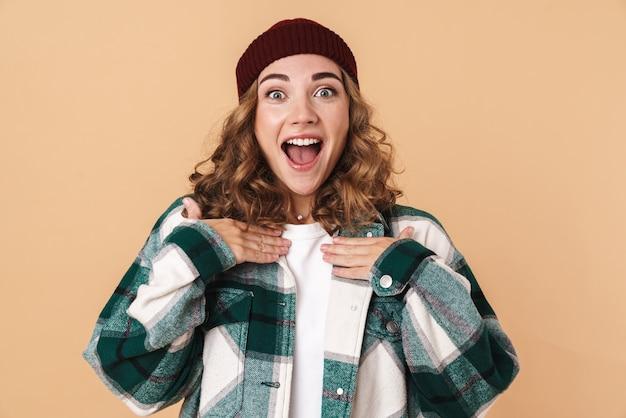 Portret bardzo podekscytowanej kobiety w czapce z dzianiny wyrażającej zaskoczenie i uśmiechniętej na białym tle nad beżową ścianą