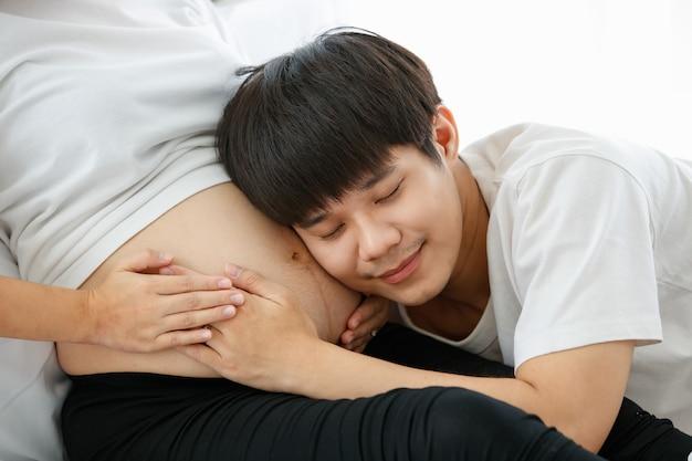 Portret bardzo szczęśliwego azjaty, który zostanie ojcem. siedzi i słucha z miłością i szczęściem dźwięku płodu w brzuchu ciężarnej żony.