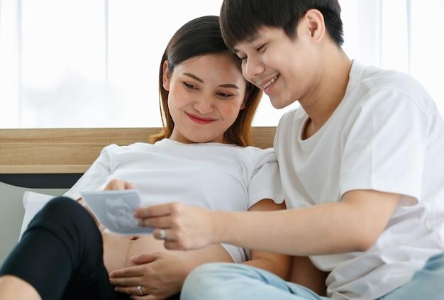 Portret bardzo szczęśliwego młodego mężczyzny azjatyckiego i kobiety w ciąży siedzącej na łóżku, uśmiechniętej i patrzącej na zdjęcie płodu z usg. szczęśliwa i zdrowa koncepcja rodziny.