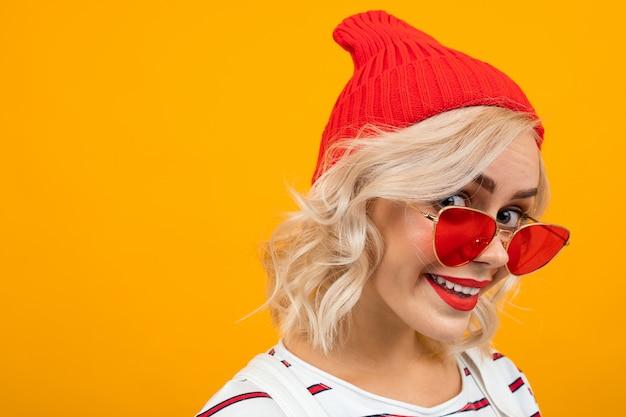 Portret bardzo uroczej uroczej dziewczyny z białymi włosami w czerwonym kapeluszu na żółtym