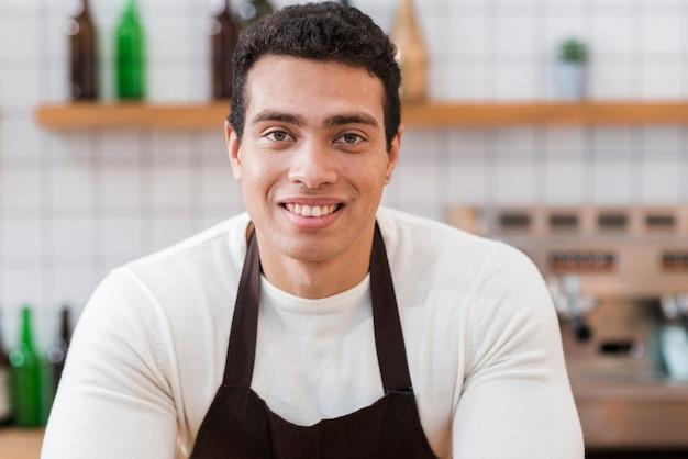 Portret barista chłopiec w kawiarni