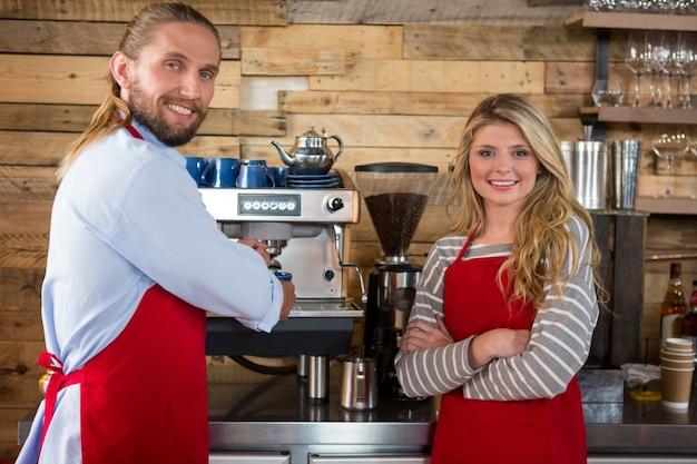 Portret baristów płci męskiej i żeńskiej stojących przy ekspresie do kawy w kawiarni