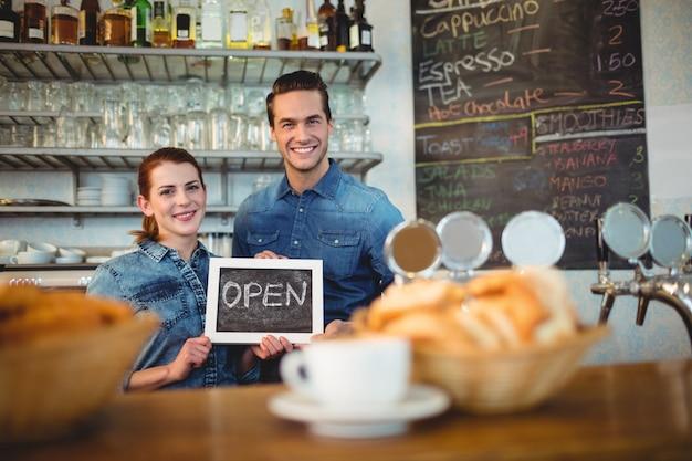Portret baristy trzyma chalkboard przy kawiarnią