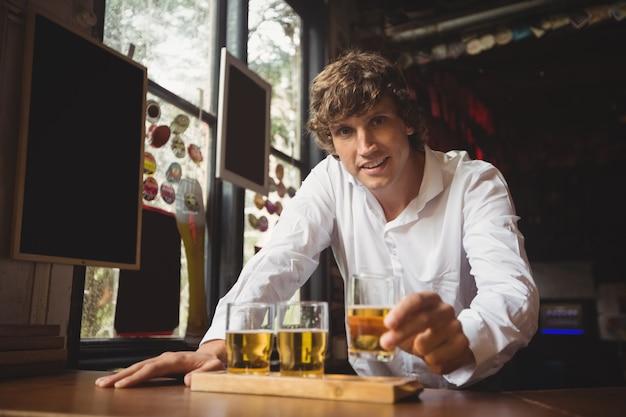 Portret barmanu mienia whisky strzelał szkło przy baru kontuarem