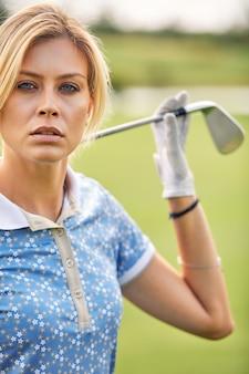 Portret bawić się golfa na zielonym polu kobieta