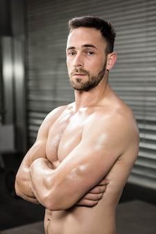 Portret bez koszuli mężczyzna z rękami krzyżował przy crossfit gym