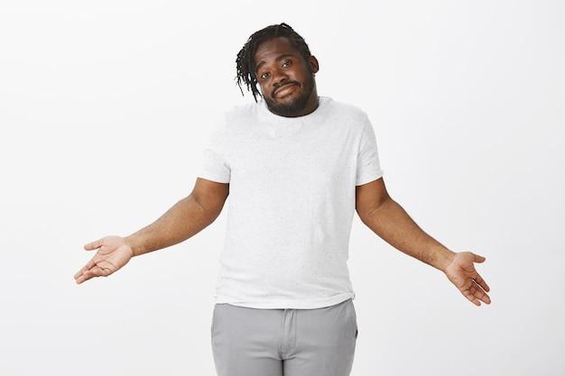 Portret beztroski facet z warkoczami, pozowanie na białej ścianie