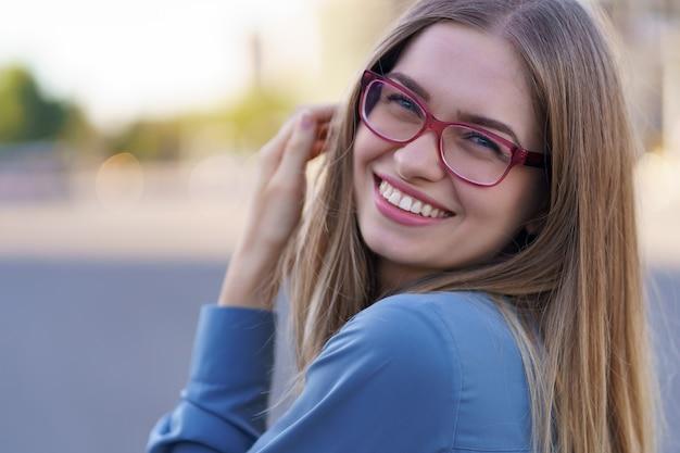 Portret beztroskiej młodej kobiety uśmiechając się z miejskiej ulicy. wesoła dziewczynka kaukaski w okularach w mieście.