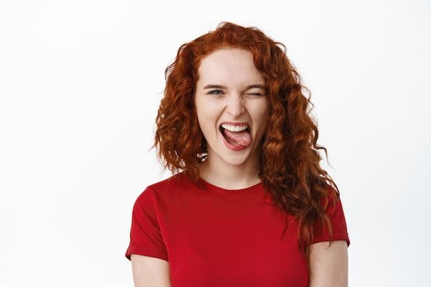 Portret beztroskiej młodej nastolatki imbirowej robi pozytywne śmieszne miny, pokazując język i uśmiechając się, mrugając, aby zmotywować i zachęcić cię, biała ściana