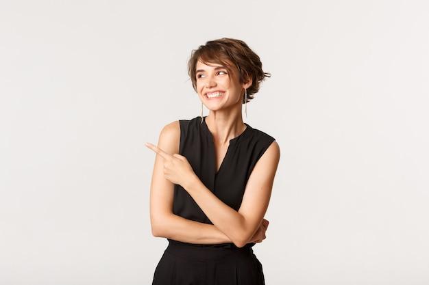 Portret beztroskiej pięknej pani w eleganckim ubraniu wskazująca i patrząca w lewy górny róg, uśmiechnięta szczęśliwa, biała.